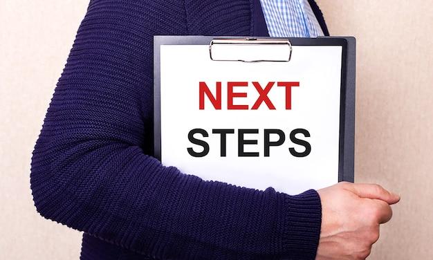 次のステップは、横に立っている男性が持っている白いシートに書かれています