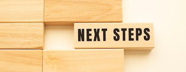 흰색 테이블에 누워 나무 스트립에 다음 단계 텍스트. 개념.