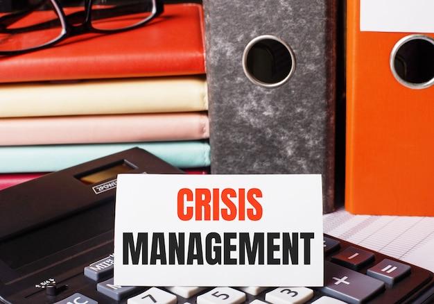 電卓のドキュメントが入った日記とフォルダの横に、crisismanagementと書かれた白いカードがあります。