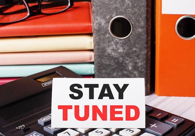 Рядом с дневниками и папками с документами на калькуляторе есть белая карточка с надписью stay tuned.