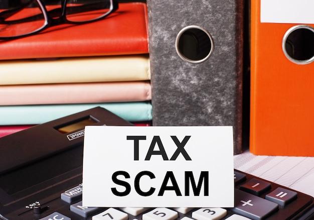 Рядом с дневниками и папками с документами на калькуляторе есть белая карточка с надписью tax scam.