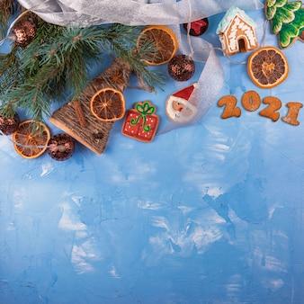 モミの枝、おもちゃの花輪、装飾が施された2021年のホリデーブルーのコンクリートの背景。クリスマスと新年あけましておめでとうございますのテーマ。フラットレイ、上面図