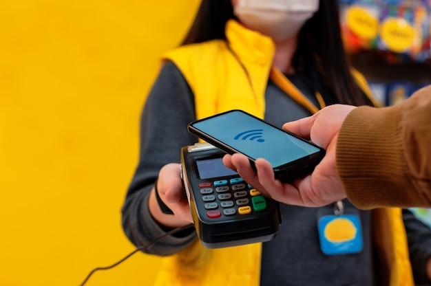 Технология nfc. покупатель-мужчина держит в руках смартфон с беспроводной оплатой. продавец в маске вируса держит в руках платежный терминал.