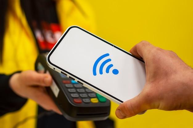Nfcテクノロジー。男性のバイヤーは、ワイヤレス決済を手にしたスマートフォンを持っています。売り手は、決済端末を手に持っています。