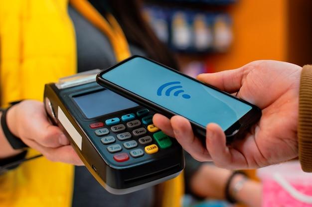 Технология nfc. покупатель-мужчина держит в руках смартфон с беспроводной оплатой. продавец держит в руках платежный терминал.