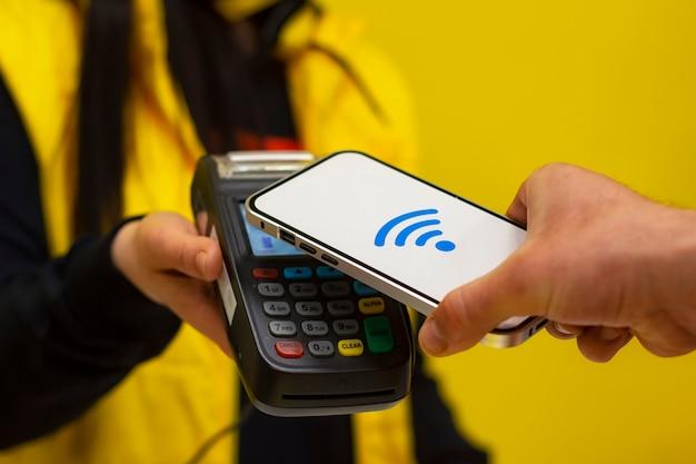Технология nfc. покупатель-мужчина держит в руках смартфон с беспроводной оплатой