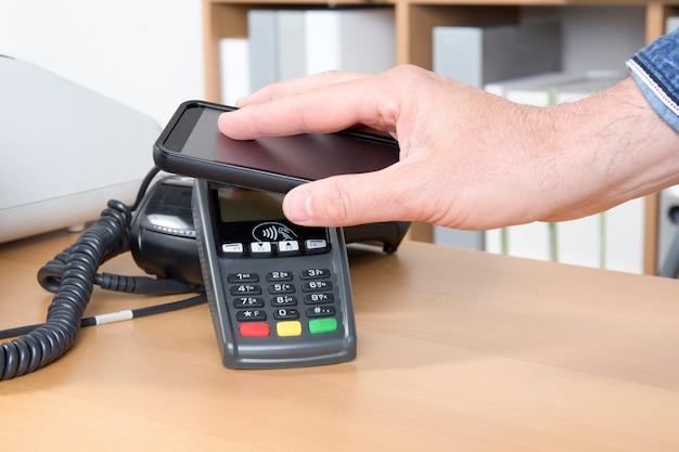 携帯電話のnfcテクノロジーでお金を払って男