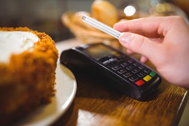 Женщина платить счета через смартфон с использованием технологии nfc