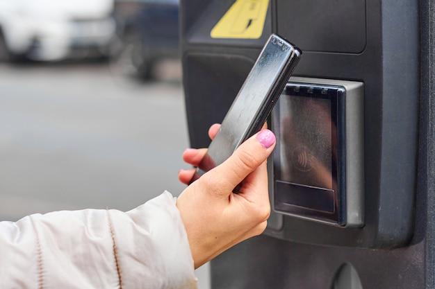 Плата за смартфон с технологией nfc для общественной парковки с копией пространства. концепция бесконтактных платежей.