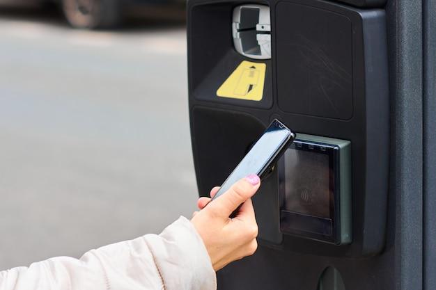 Молодая женщина платит за парковку, используя nfc в своем смартфоне. бесконтактный способ оплаты с копией пространства