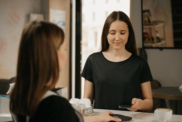 Девушка платит за кофе с помощью смартфона по бесконтактной технологии nfc в кафе