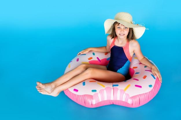 巨大なnflatedゴムリングと青い水着と麦わら帽子でかわいい女の子
