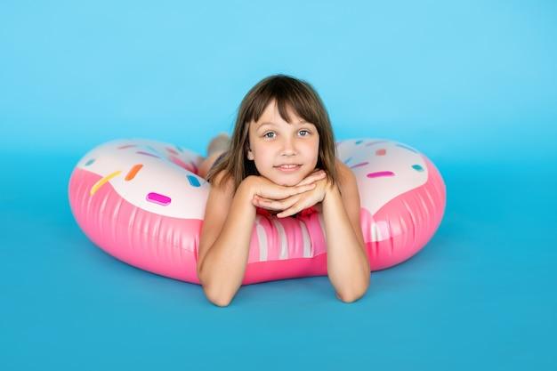 巨大なnflatedラバーリングと青い水着でかわいい女の子
