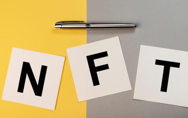 黄色と灰色の背景の紙のノートのnft頭字語