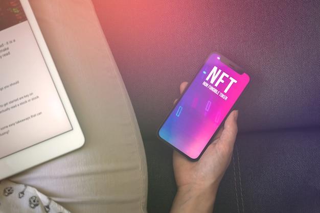 Крипто-искусство nft. будущее внештатной концепции фона. торговля женщина с невзаимозаменяемым токеном на мобильном телефоне. логотип на экране фото