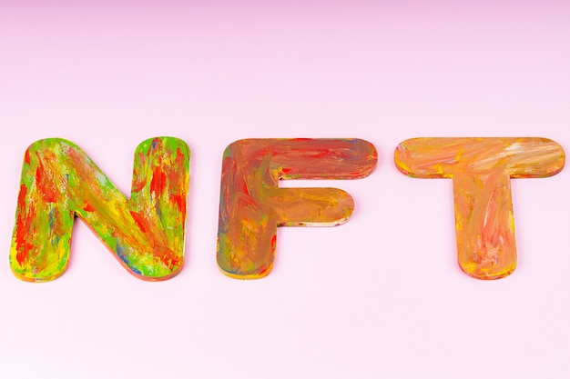 Надпись nft на розовом фоне. незаменимый жетон, состоящий из разноцветных букв, вид сверху. крипто-арт-концепция