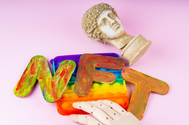 Не взаимозаменяемый токен nft. концепция системы блокчейн. классическая статуя и игрушка pop it на розовом фоне. крипто-арт-концепция с искусственной рукой