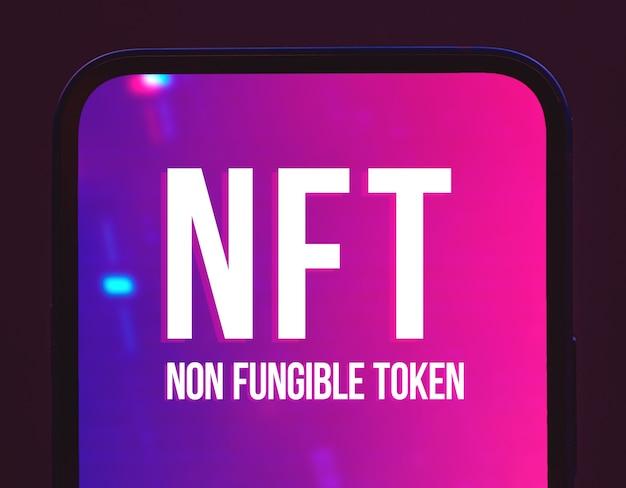 Nft невзаимозаменяемый токен крипто-арт логотип на экране современного мобильного телефона, крупный план, фото концепции блокчейна