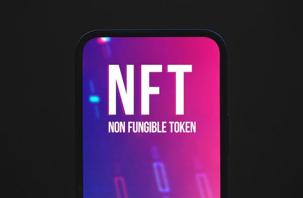 Фон концепции невзаимозаменяемых токенов nft, логотип на экране современного мобильного телефона, фото вида сверху
