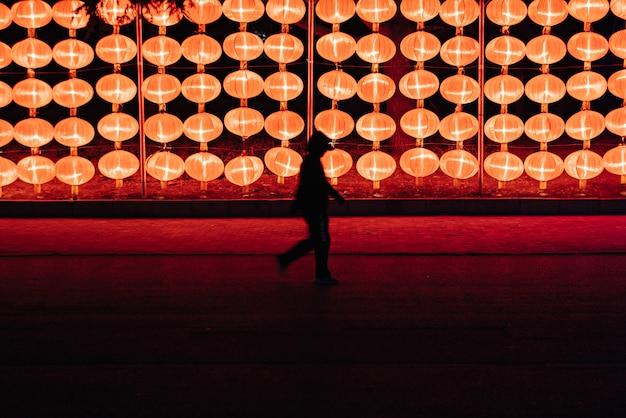 中国北東部大連市のngihtにあるランタンランプの近くを歩く人のシルエット