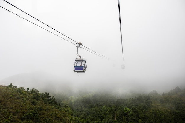Ngong ping 360 cable car on the green mountain landscape view in the rain season hong kong