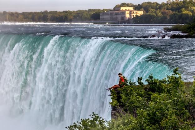 Ниагарский водопад, канада молодые женщины сидят на краю и смотрят на водопад