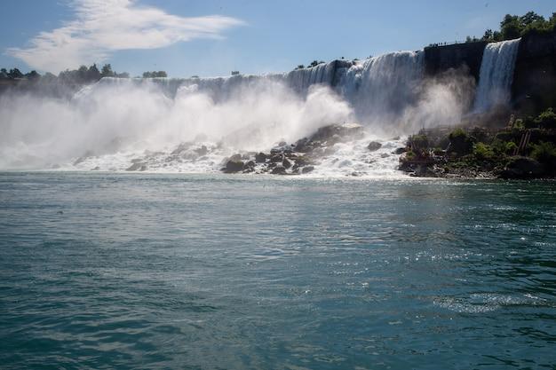 나이아가라 폭포는 미국의 푸른 하늘과 햇빛 아래 녹지로 덮여 있습니다.