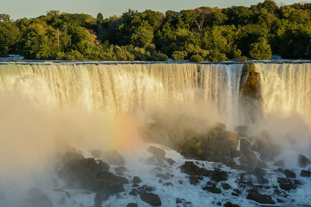 Ниагарский водопад во время восхода солнца. красивая разноцветная радуга на фоне водопада