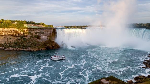Ниагарский водопад в канаде, круизная лодка с туристами, приближающимися к водопаду подкова