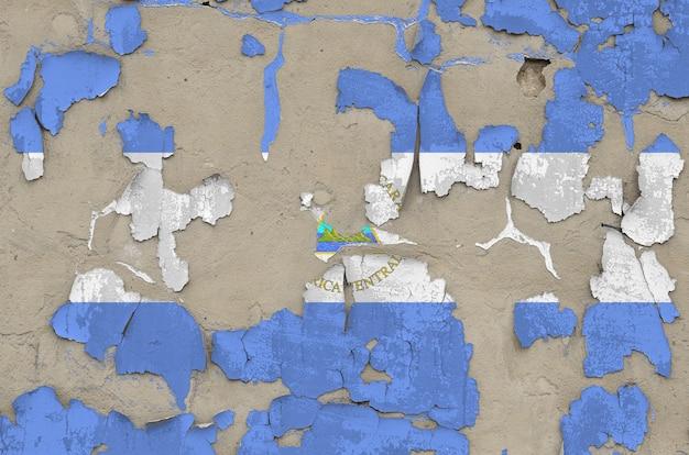 古い時代遅れの乱雑なコンクリート壁のクローズアップのペンキ色で描かれたニカラグアの旗。