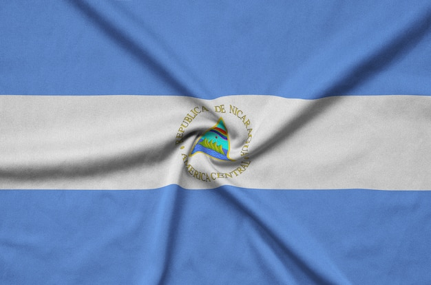 Nicaragua flag  is depicted on a sports cloth fabric with many folds.