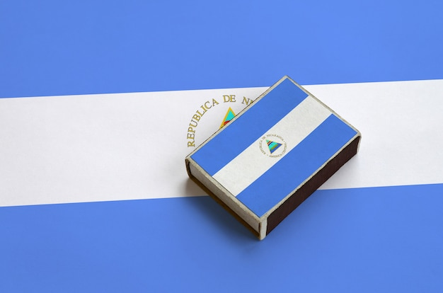 Nicaragua flag  is pictured on a matchbox that lies on a large flag
