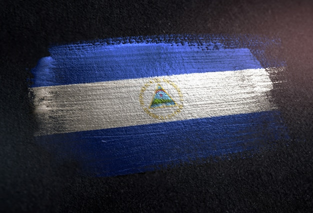 Nicaragua flag made of metallic brush paint on grunge dark wall