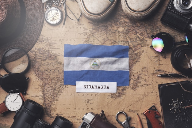 Nicaragua flag between traveler's accessories on old vintage map. overhead shot