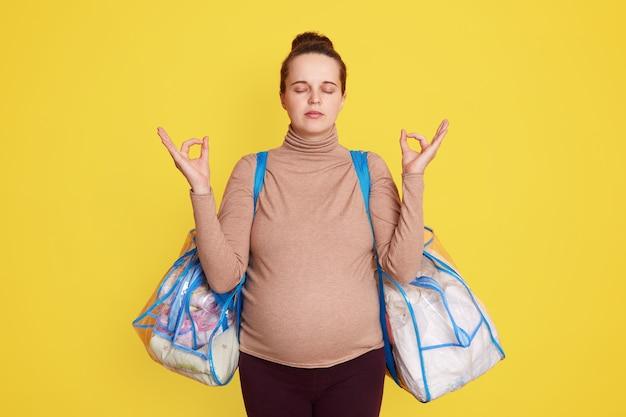 Милая очаровательная спокойная милая красивая будущая мама в повседневной одежде, с пучком волос, позирует на фоне желтой стены с сумками для роддома, пытается расслабиться и не волноваться перед родами.