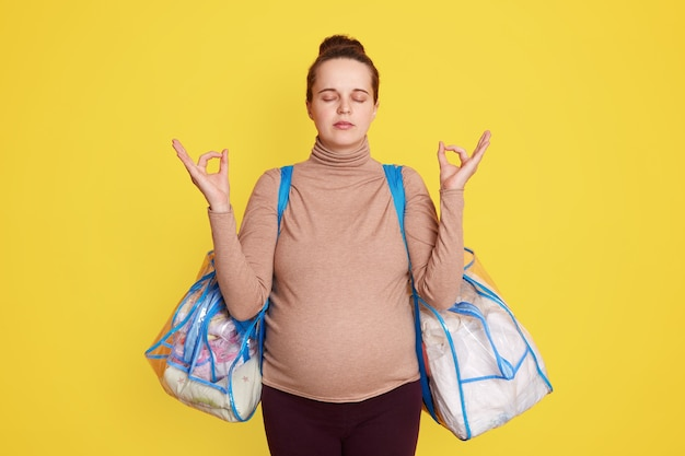 Nice adorable calm lovely beautiful expectant mom wearing casual attire, has hair bun, posing against yellow wall with bags for maternity hospital, trying to relax and not worry before giving birth.