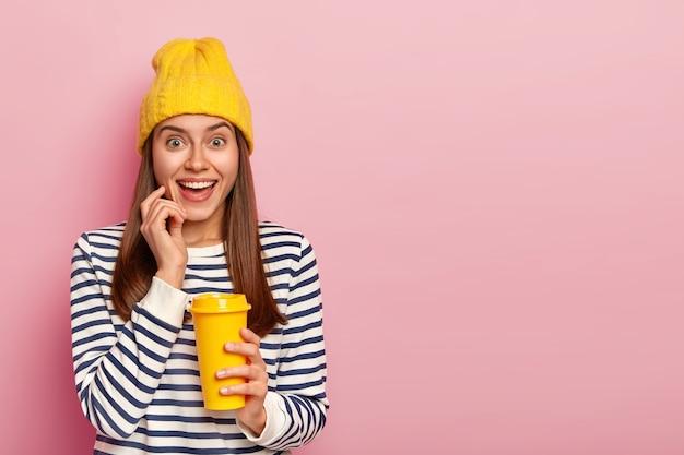 素敵な愛らしい女性は、紙コップのコーヒーを保持し、黄色い帽子とストライプのセーターを着て、広く笑顔で、自然の美しさを持ち、ピンクの壁に隔離されています