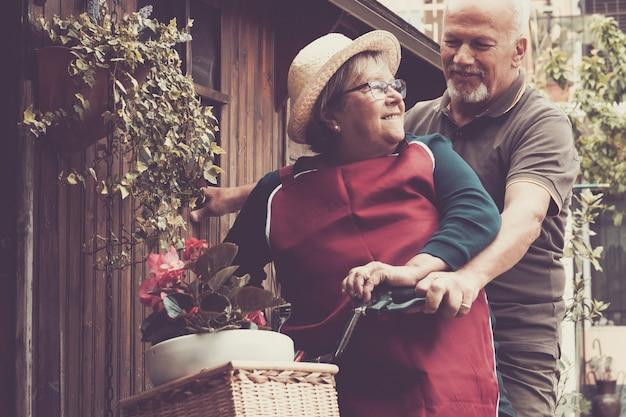 좋은 성인 백인 남자와 여자 커플 웃으면 서 집에서 정원에서 자전거를 타고 함께 재미를. 자연스러운 행복한 라이프 스타일-