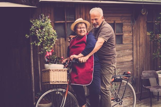 素敵な大人の白人の2人の男性と女性のカップルが笑い、自宅の庭で自転車に乗って一緒に楽しんでいます。オフィスでの仕事の後の一体感のある生活のための自然な幸せなライフスタイル