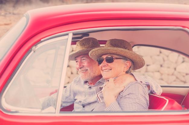 Хорошие взрослые пары обнимаются и любят внутри красного старого старинного автомобиля, припаркованного на дороге. улыбается и веселится, путешествуя вместе. счастье и образ жизни для хороших людей. летнее время и отпуск