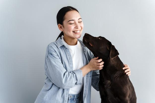 犬をかわいがり、灰色の背景で笑っている素敵な愛情のこもった女性