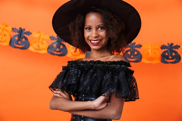Nice african american girl in black halloween costume looking at camera and smiling isolated over orange pumpkin wall