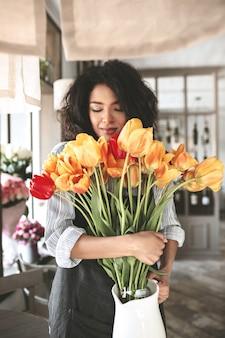 手にチューリップの花束を持って立っている素敵なアフリカ系アメリカ人の女の子。花で目を閉じて思慮深く暗い巻き毛の女性の肖像画
