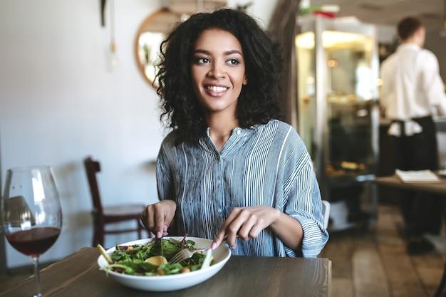 레스토랑에서 먹는 검은 곱슬 머리를 가진 좋은 아프리카 계 미국인 여자