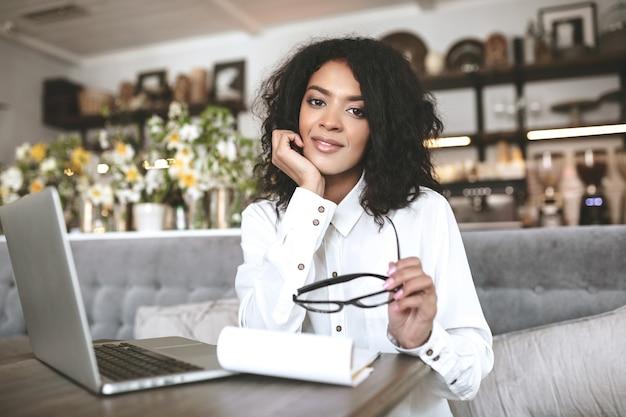 ノートパソコンとノートブックを持ってレストランで働いている素敵なアフリカ系アメリカ人の女の子。手に眼鏡をかけてカフェに座っているかわいい女の子