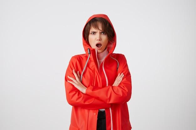 빨간 비옷을 입은 멋진 깜짝 놀라게 한 젊은 짧은 머리 아가씨는 크게 열린 입으로 감탄스럽게 보입니다. 교차 팔로 서.
