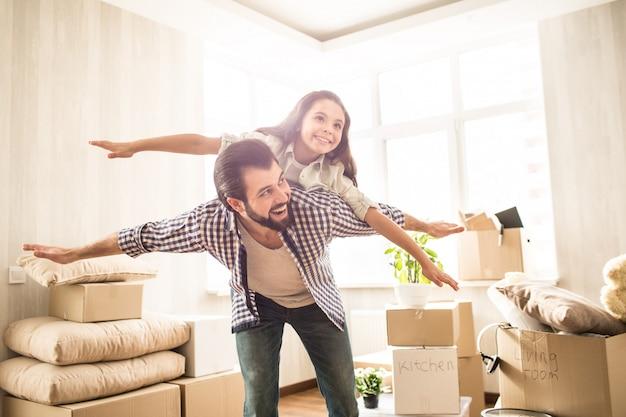 Славная и красивая картина отца и дочери проводя время совместно. девушка лежит на спине отца и делает вид, что летит. ее папа делает то же самое. они оба счастливы.