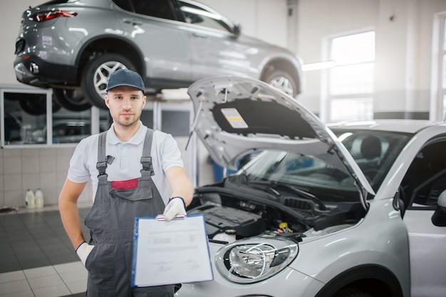 素敵で自信を持って若い男が車に立っています。彼はそれに書類が入ったプラスチック製のフォルダーを持っています。