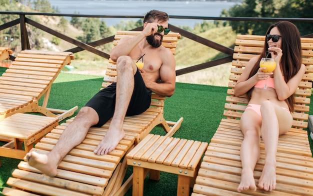 Хорошая и позитивная пара лежит на лежаках и держит в руках коктейли. они смотрят друг на друга и носят солнцезащитные очки. попли счастливы.