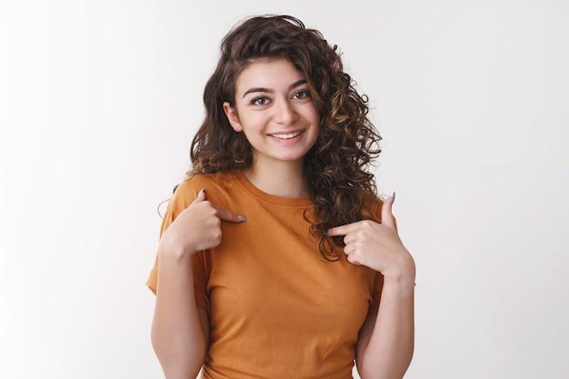 Милая армянская кудрявая девушка хвастается собственными достижениями, указывая на себя, прижимая указательные пальцы к груди, счастливо улыбается, представляет перед собой новых сотрудников, стоя на белом фоне расслабленно и общительно